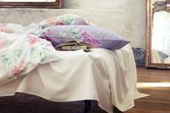 Ein bezauberndes Ensemble bilden das üppige Bouquet und die formvollendete Blüte von Flieder, das sich bei der Bettwäsche LARA `blanc´und `viola´ lieblich duftend als großzügiges All-Over-Dessin auf einfarbig weißem oder lila Grund anordnet.
