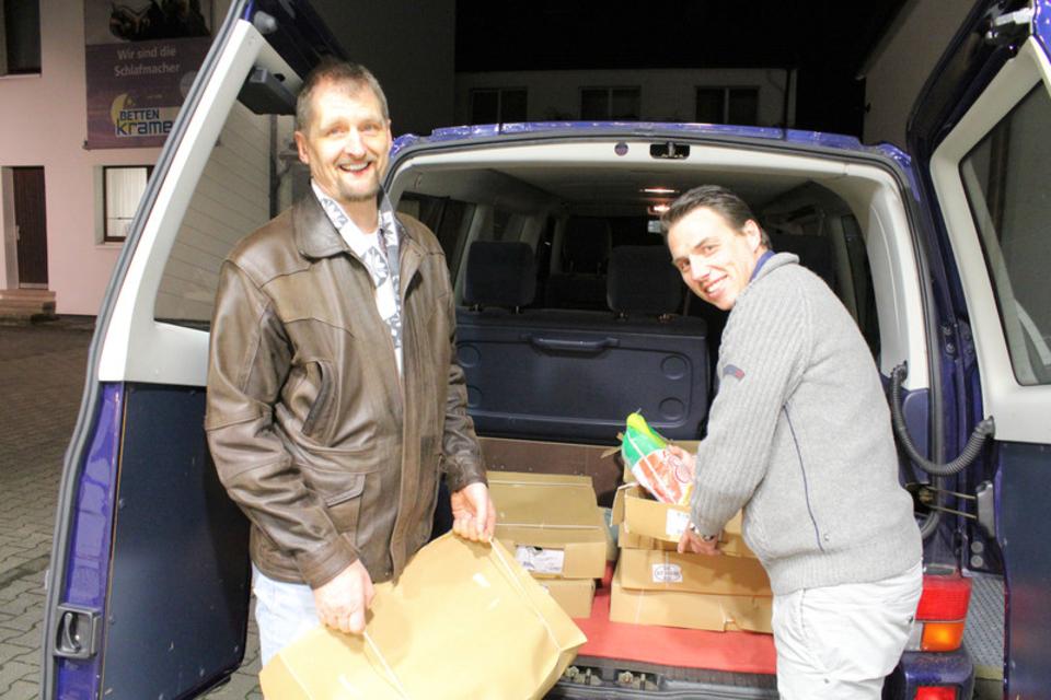 2 Personen an einem Fahrzeug mit Spenden